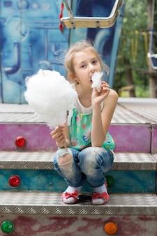 Młoda dziewczyna delektuje się watą cukrową