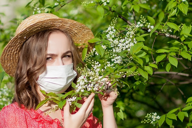 Młoda dziewczyna dmuchanie nosa i kichanie w tkance przed kwitnącym drzewem. sezonowe alergeny wpływające na ludzi. piękna dama ma nieżyt nosa.