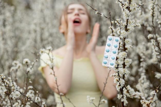 Młoda dziewczyna dmuchanie nosa i kichanie w tkance przed kwitnącym drzewem. sezonowe alergeny wpływające na ludzi. piękna dama ma nieżyt nosa