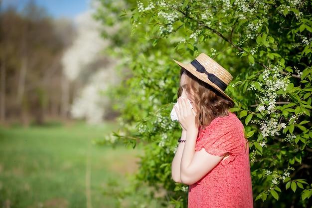 Młoda dziewczyna dmuchanie w nos i kichanie w tkance przed kwitnącym drzewem. sezonowe alergeny dotykające ludzi. piękna pani ma nieżyt nosa.