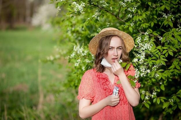 Młoda dziewczyna dmuchanie w nos i kichanie w tkance przed kwitnącym drzewem