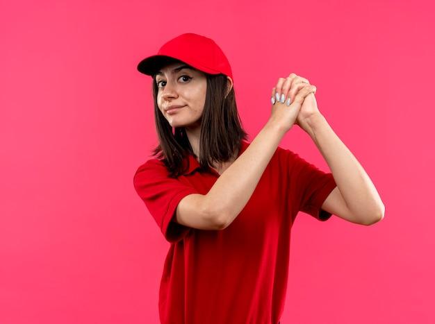 Młoda dziewczyna dostawy na sobie czerwoną koszulkę polo i czapkę, trzymając się za ręce razem, wykonując gest pracy zespołowej, patrząc pewnie stojąc na różowym tle