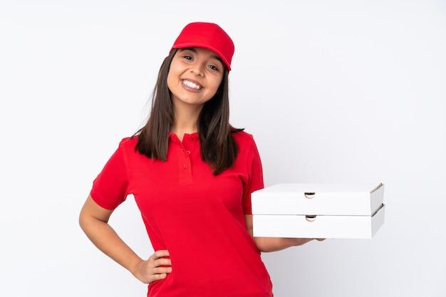 Młoda dziewczyna dostawy pizzy na białym pozowanie z rękami na biodrze i uśmiechnięte
