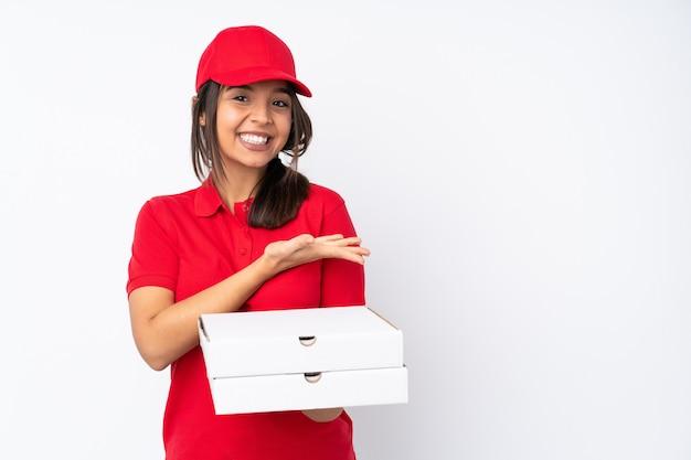 Młoda dziewczyna dostawy pizzy na białym przedstawiając pomysł, patrząc uśmiechając się w kierunku