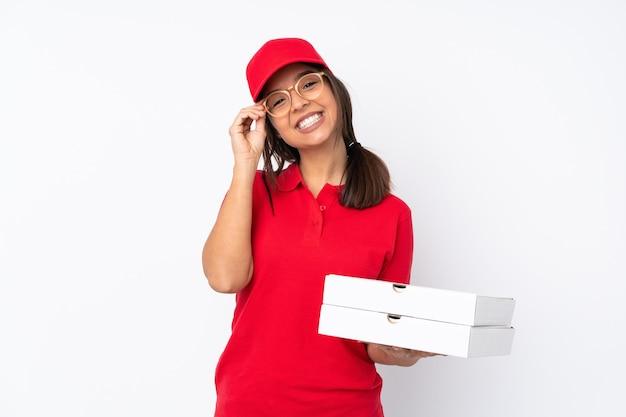 Młoda dziewczyna dostawy pizzy na białym tle w okularach i szczęśliwy