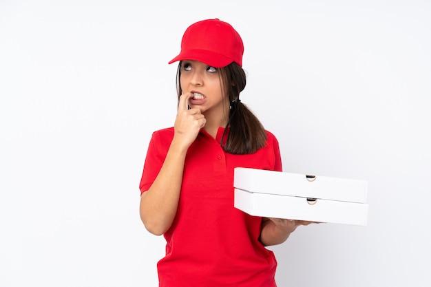 Młoda dziewczyna dostawy pizzy na pojedyncze białe ściany nerwowe i przerażone