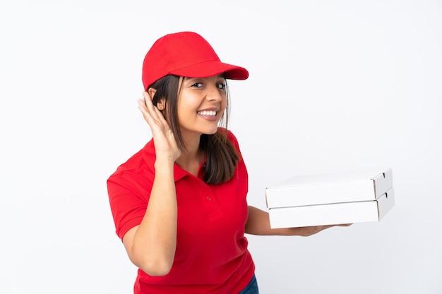 Młoda dziewczyna dostawy pizzy na pojedyncze białe ściany słuchając czegoś, kładąc rękę na uchu