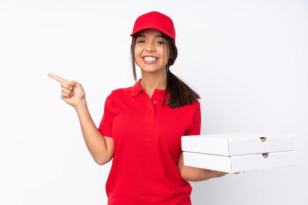 Młoda dziewczyna dostawy pizzy na pojedyncze białe tło, wskazując palcem w bok