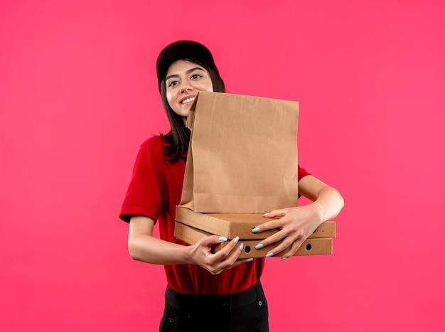 Młoda dziewczyna dostawy ubrana w czerwoną koszulkę polo i czapkę trzymająca papierowy pakiet i ospy pizzy patrząc na bok z uśmiechem na twarzy stojącej na różowym tle