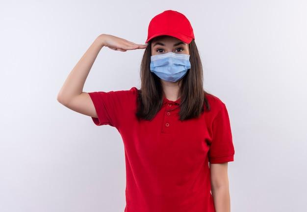 Młoda dziewczyna dostawy ubrana w czerwoną koszulkę w czerwonej czapce nosi maskę i salutuje na odosobnionym białym tle