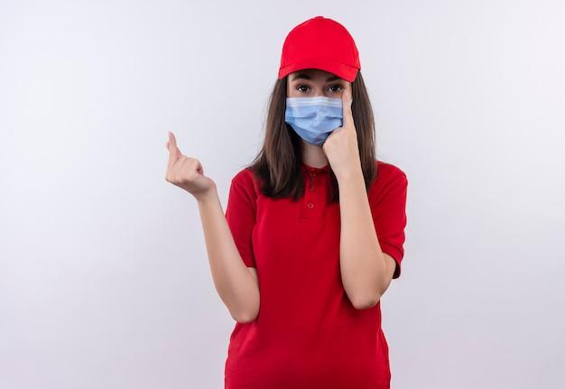 Młoda dziewczyna dostawy ubrana w czerwoną koszulkę w czerwonej czapce nosi maskę na twarz poprosić o wskazówkę na na białym tle