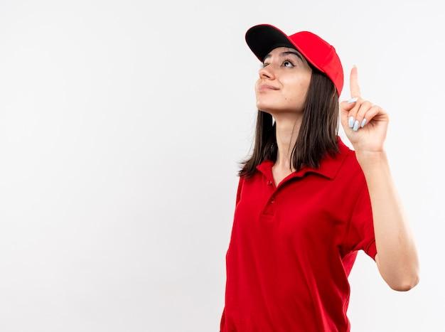 Młoda dziewczyna dostawy ubrana w czerwony mundur i czapkę patrząc w górę pokazując palec wskazujący uśmiechnięty pewnie stojąc na białym tle