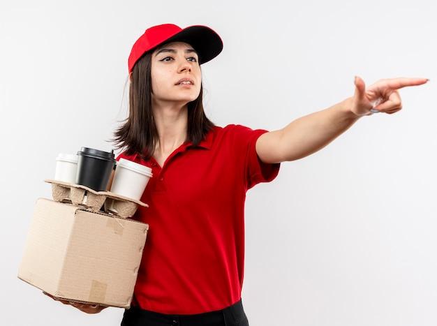 Młoda dziewczyna dostawy ubrana w czerwony mundur i czapkę, trzymając pakiet pole i filiżanki kawy patrząc na bok, wskazując na coś z palcem wskazującym stojącym na białym tle