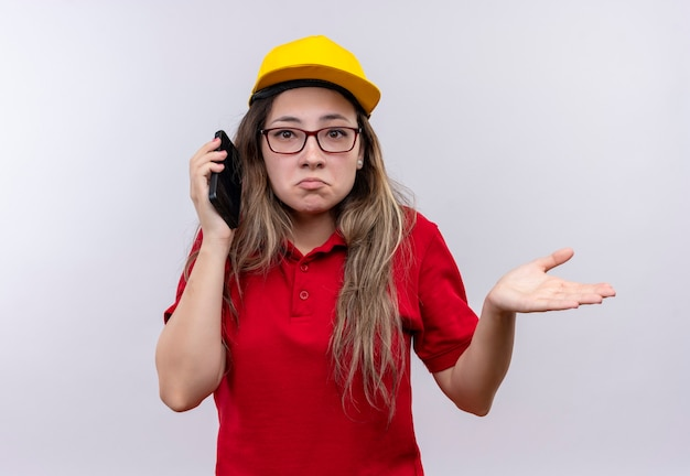 Młoda dziewczyna dostawy w czerwonej koszulce polo i żółtej czapce rozmawia przez telefon komórkowy, patrząc zdezorientowany wzruszając ramionami