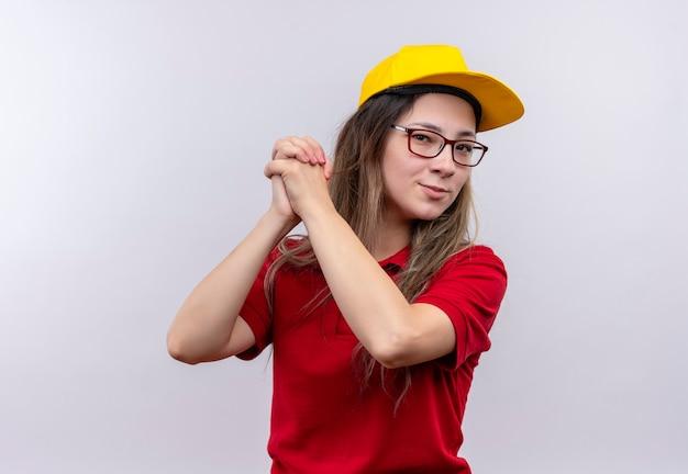 Młoda dziewczyna dostawy w czerwonej koszulce polo i żółtej czapce, ściskając dłoń, uśmiechając się gestem pracy zespołowej