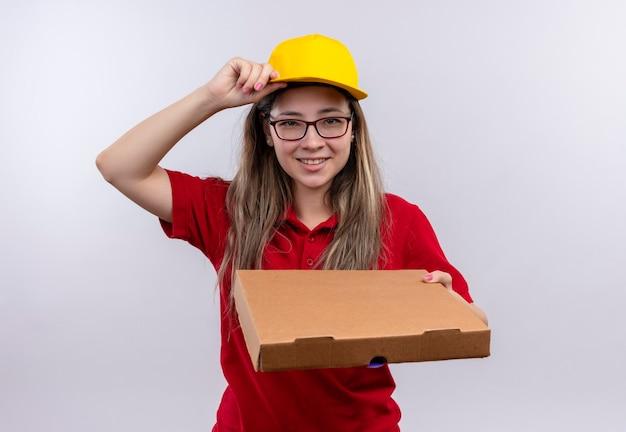 Młoda dziewczyna dostawy w czerwonej koszulce polo i żółtej czapce trzyma pudełko po pizzy, patrząc pewnie, uśmiechając się, dotykając jej czapki