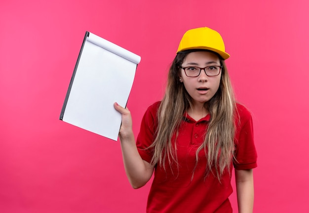 Młoda dziewczyna dostawy w czerwonej koszulce polo i żółtej czapce trzyma schowek z pustymi stronami, patrząc rozczarowany