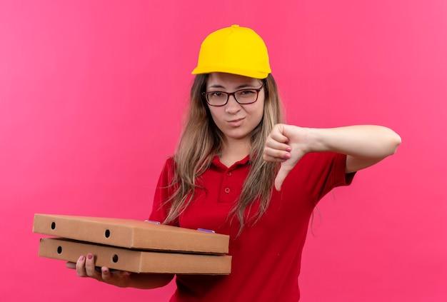 Młoda dziewczyna dostawy w czerwonej koszulce polo i żółtej czapce trzyma stos pudełek po pizzy pokazując niechęć