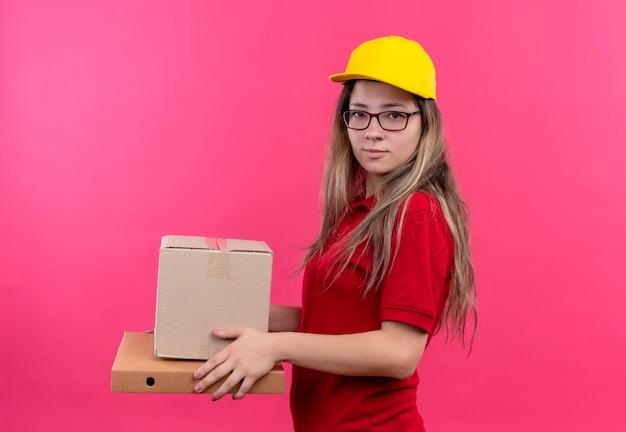 Młoda dziewczyna dostawy w czerwonej koszulce polo i żółtej czapce, trzymając pudełko pakiet i pudełko pizzy patrząc na kamery z poważnymi wyrażeniami pewności siebie