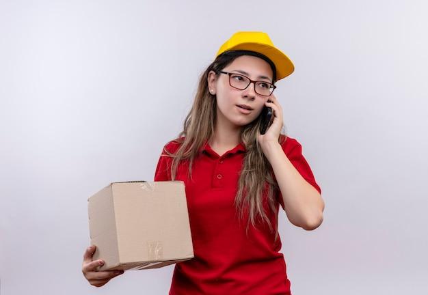 Młoda dziewczyna dostawy w czerwonej koszulce polo i żółtej czapce, trzymając pudełko pakiet podczas rozmowy na telefon komórkowy z poważną miną
