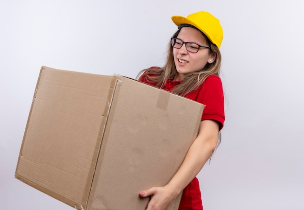 Młoda dziewczyna dostawy w czerwonej koszulce polo i żółtej czapce trzymającej pudełko wygląda źle cierpiących na wagę pudełka