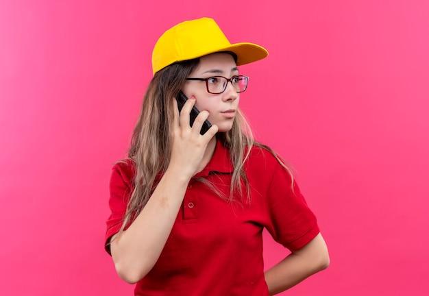 Młoda dziewczyna dostawy w czerwonej koszulce polo i żółtej czapce wygląda niespokojnie podczas rozmowy przez telefon komórkowy
