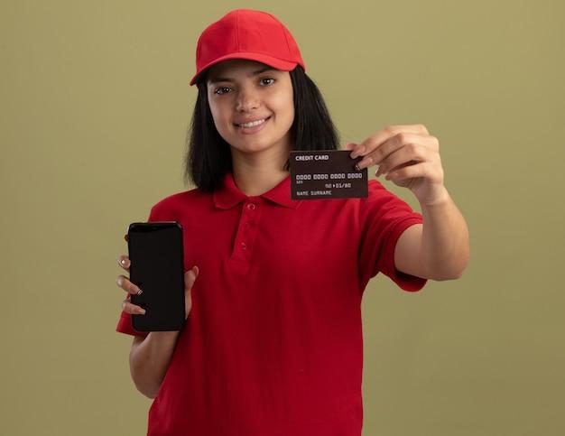 Młoda dziewczyna dostawy w czerwonym mundurze i czapce, trzymając smartfon pokazując kartę kredytową, uśmiechając się wesoło stojąc nad jasną ścianą