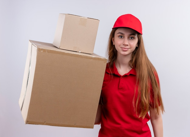 Młoda dziewczyna dostawy w czerwonym mundurze, trzymając pola na na białym tle białej ścianie