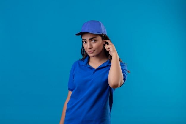Młoda dziewczyna dostawy w niebieskim mundurze i czapce drapiąca głowę patrząc na kamery ze zdezorientowanym wyrazem twarzy mającej wątpliwości stojąc na niebieskim tle