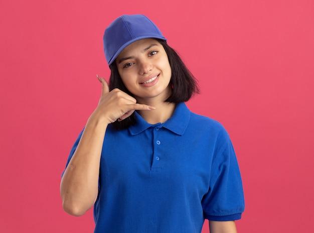 Młoda dziewczyna dostawy w niebieskim mundurze i czapce dzwoniąc do mnie, uśmiechając się stojąc nad różową ścianą