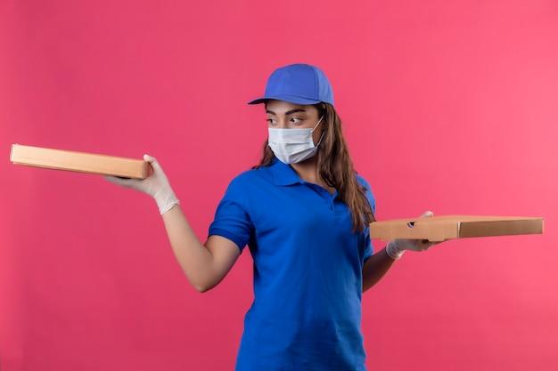 Młoda dziewczyna dostawy w niebieskim mundurze i czapce na sobie maskę ochronną na twarz i rękawiczki, trzymając pudełka po pizzy patrząc na bok z poważną twarzą stojącą na różowym tle