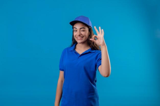 Młoda dziewczyna dostawy w niebieskim mundurze i czapce patrząc na aparat mrugając, uśmiechając się radośnie robi ok znak stojąc na niebieskim tle