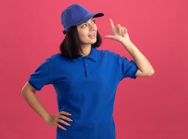 Młoda dziewczyna dostawy w niebieskim mundurze i czapce patrząc na bok z radością i emocjami, pokazując palec wskazujący o nowym świetnym pomyśle stojącym nad różową ścianą