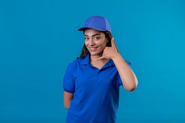 Młoda dziewczyna dostawy w niebieskim mundurze i czapce patrząc na kamery uśmiechnięty pewnie, że zadzwoń do mnie gest stojąc na niebieskim tle
