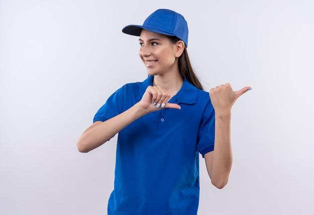 Młoda dziewczyna dostawy w niebieskim mundurze i czapce szczęśliwa i pozytywna, wskazując palcami na bok