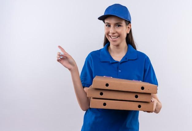 Młoda dziewczyna dostawy w niebieskim mundurze i czapce trzyma pudełka po pizzy, wskazując palcem na bok, uśmiechając się szeroko z radosną buźkę