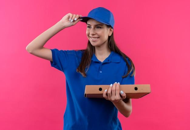 Młoda dziewczyna dostawy w niebieskim mundurze i czapce trzyma pudełko po pizzy patrząc na bok, uśmiechając się radośnie