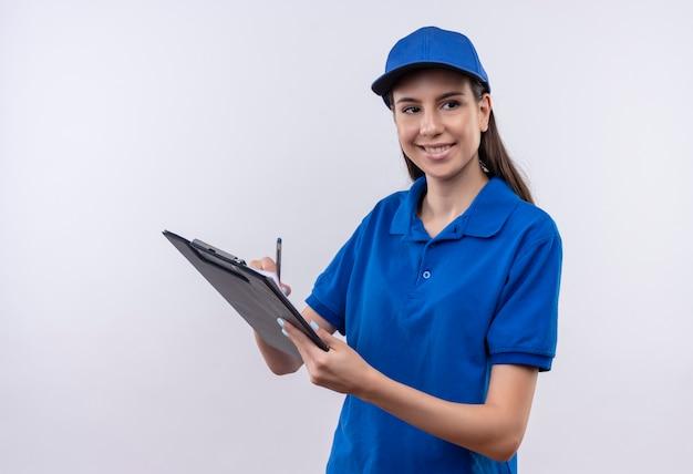 Młoda dziewczyna dostawy w niebieskim mundurze i czapce trzyma schowek i pióro patrząc na bok z pewnym uśmiechem na twarzy