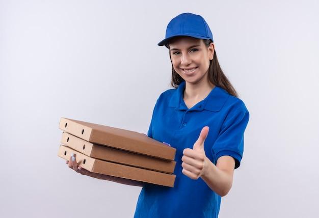 Młoda dziewczyna dostawy w niebieskim mundurze i czapce trzyma stos pudełek po pizzy patrząc na kamery z pewnym uśmiechem na twarzy pokazując kciuki do góry