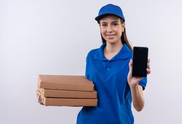 Młoda dziewczyna dostawy w niebieskim mundurze i czapce trzyma stos pudełek po pizzy pokazując smartfon uśmiechnięty pewnie