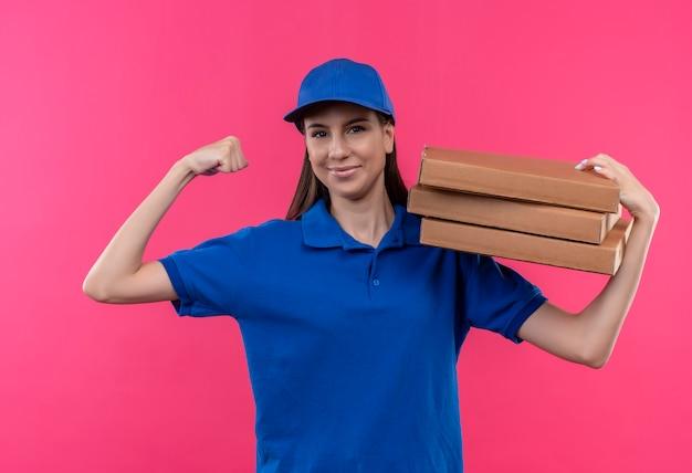 Młoda dziewczyna dostawy w niebieskim mundurze i czapce trzyma stos pudełek po pizzy, uśmiechając się pewnie, podnosząc pięść uśmiechnięty pewnie