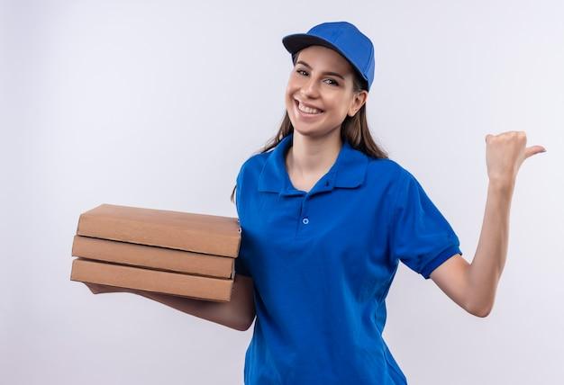 Młoda dziewczyna dostawy w niebieskim mundurze i czapce trzyma stos pudełek po pizzy, wskazując z powrotem kciukiem, uśmiechając się radośnie