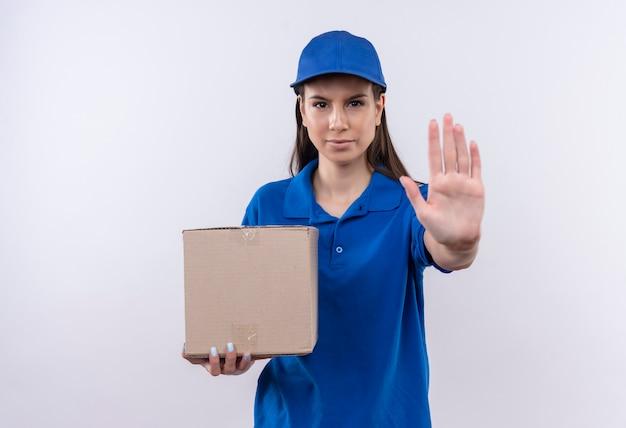 Młoda dziewczyna dostawy w niebieskim mundurze i czapce, trzymając pakiet pole, co znak stopu ręką patrząc na kamery z poważną miną
