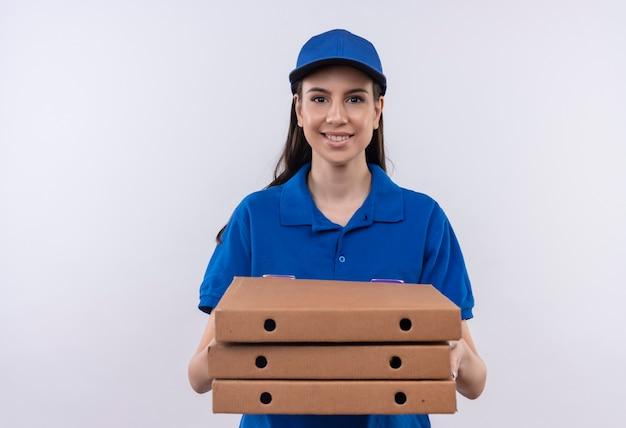 Młoda dziewczyna dostawy w niebieskim mundurze i czapce trzymając stos pudełek po pizzy patrząc na kamery z pewnym uśmiechem na twarzy