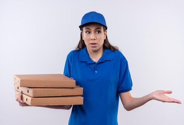 Młoda dziewczyna dostawy w niebieskim mundurze i czapce, trzymając stos pudełek po pizzy, patrząc niepewnie i zdezorientowany wzruszając ramionami