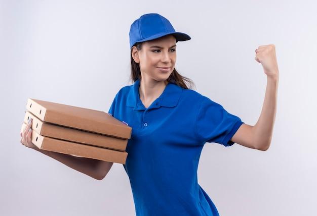 Młoda dziewczyna dostawy w niebieskim mundurze i czapce, trzymając stos pudełek po pizzy, patrząc pewnie zaciskając pięść, koncepcja zwycięzcy