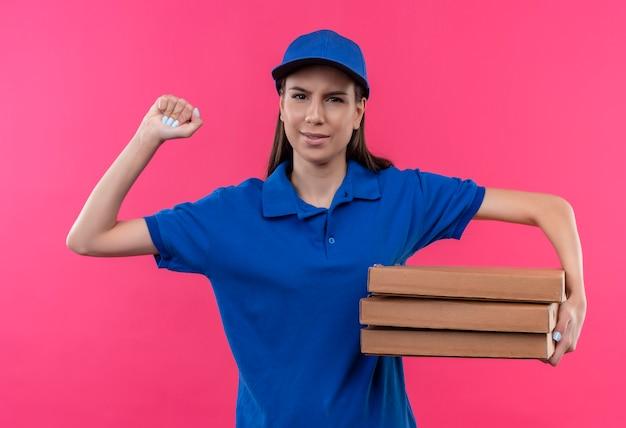 Młoda dziewczyna dostawy w niebieskim mundurze i czapce trzymając stos pudełek po pizzy, podnosząc pięść patrząc na kamery z poważną miną