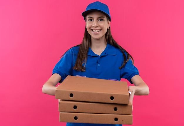 Młoda dziewczyna dostawy w niebieskim mundurze i czapce trzymając stos pudełek po pizzy uśmiechnięty pewnie patrząc na kamery