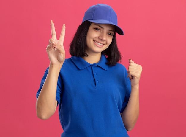 Młoda dziewczyna dostawy w niebieskim mundurze i czapce uśmiechnięta, pokazująca znak v zaciskająca pięść szczęśliwa i pozytywna stojąca nad różową ścianą