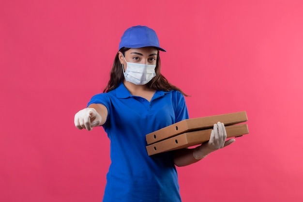 Młoda dziewczyna dostawy w niebieskim mundurze i czapce w masce ochronnej na twarz i rękawiczkach trzymająca pudełka po pizzy, wskazując palcem na aparat z poważną twarzą stojącą na różowym tle